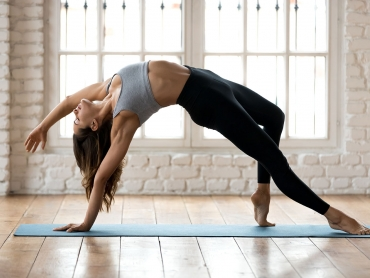 Young sporty yogi woman practicing yoga, doing Wild Thing, Flip-the-Dog exercise, Camatkarasana pose, working out, wearing sportswear, black pants and top, indoor full length, white yoga studio